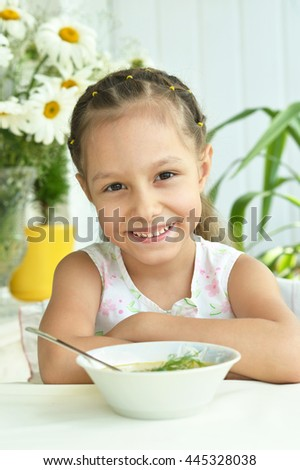 Beautiful little girl with soup - stock photo