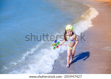 beautiful little girl with toy runs along the beach, summer, wind, waves
