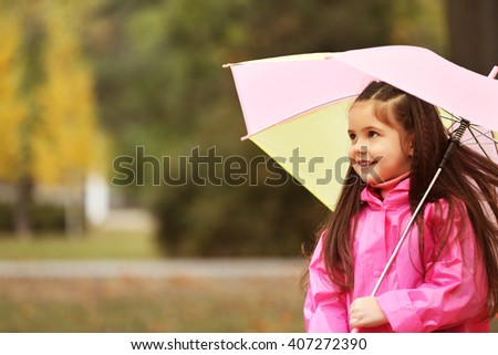 Beautiful little girl with umbrella in park - stock photo