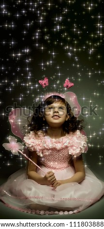 beautiful  little girl with wings, sit and  smile on dark background - stock photo
