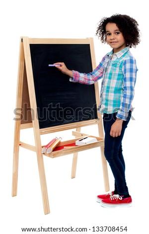 Beautiful little girl writing on classroom board. - stock photo