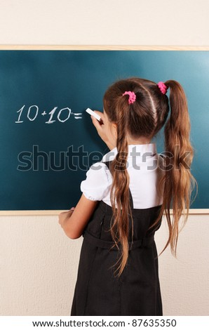 beautiful little girl writing on classroom board - stock photo