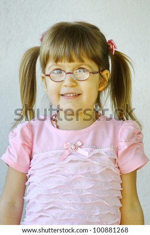 Beautiful little girl 4 years old wearing glasses in a pink dress - stock photo