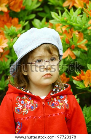 Beautiful little girl 3 years old wearing glasses  in denim jeans cap and red jacket on flower background - stock photo