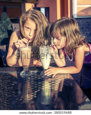 Beautiful Little girls drinking tasty milk cocktails at outdoor cafe on sunset - stock photo