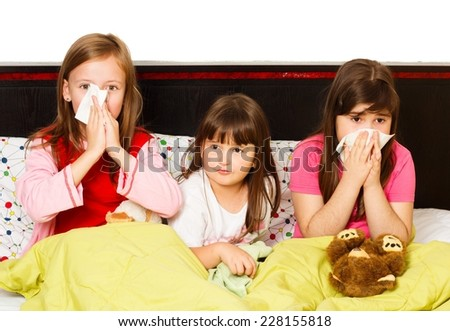 Beautiful little girls having fever and blowing their nose. - stock photo