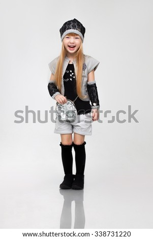 Beautiful little happy redhead girl model standing posing in studio white background in stylish modern daily autumn outfit.