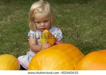 Beautiful little kid girl having fun with farming on organic pumpkin patch