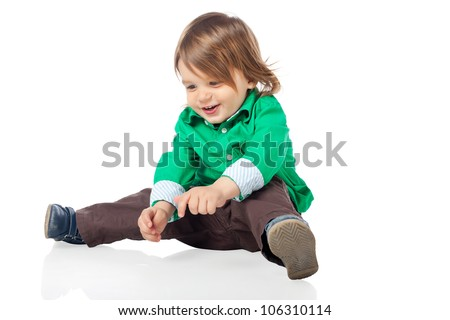 Beautiful little kid, 2 years old boy, sitting on the floor and playing, wearing shirt and jeans. High resolution image isolated on white background with copy space. Studio shot. - stock photo