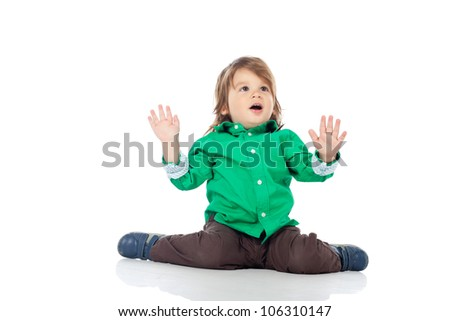 Beautiful little kid, 2 years old boy, sitting on the floor with hands up, wearing shirt and jeans. High resolution image isolated on white background with copy space. Studio shot.