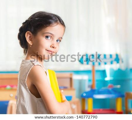 Beautiful little latin girl portrait in daycare - stock photo