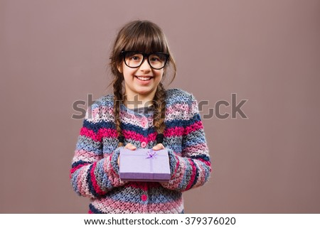 Beautiful little nerdy girl is holding gift box.Gift for you! - stock photo