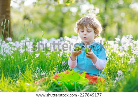 Beautiful little preschool boy having fun with traditional Easter egg hunt on warm sunny day, outdoors. Celebrating Easter holiday.