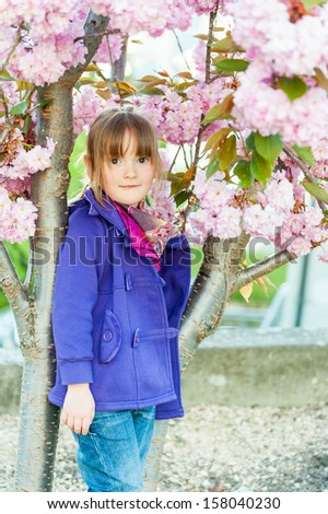Beautiful little preschool girl standing next to blooming japanese Cherry