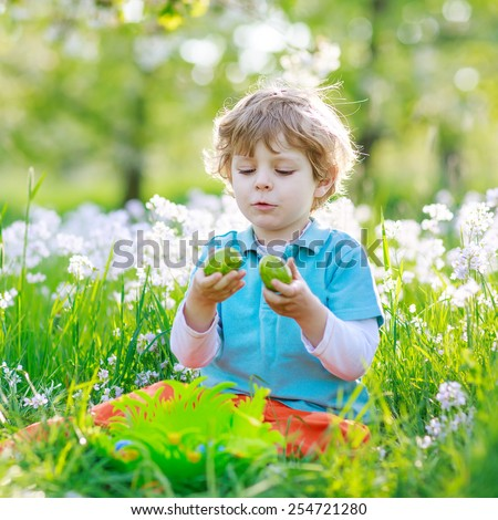 Beautiful little preschoool boy having fun with traditional Easter egg hunt on warm sunny day, outdoors. Celebrating Easter holiday. - stock photo