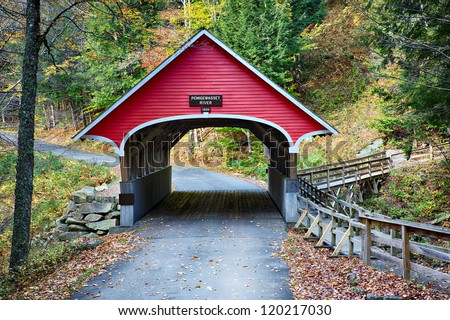 Beautiful little red covered bridge in New Hampshire during Fall season - stock photo