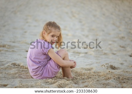 Beautiful little sad girl sitting on sand public beach. - stock photo