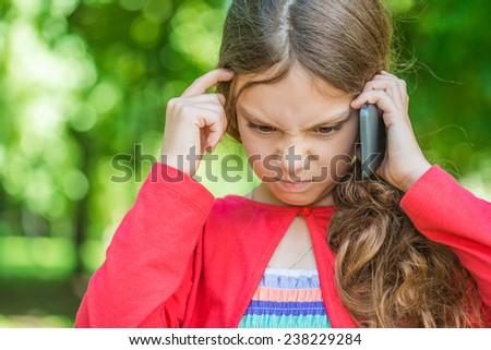 Beautiful little sad talking on phone in summer city park. - stock photo