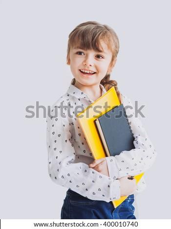 Beautiful little schoolgirl isolated on gray background - stock photo