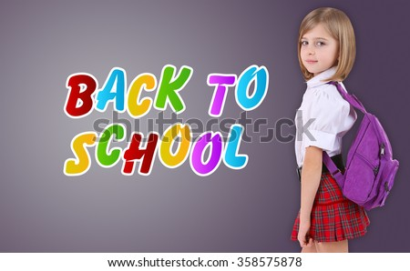 Beautiful little schoolgirl on grey background - stock photo
