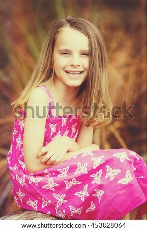 Beautiful little smiling girl portrait sitting  - stock photo