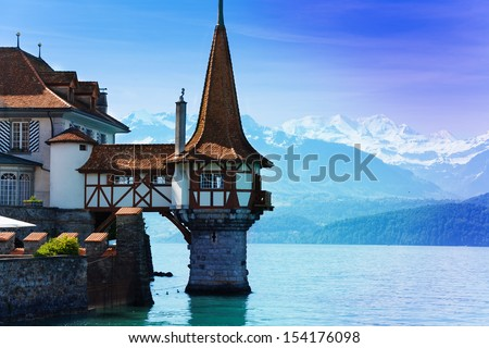 Beautiful little tower of Oberhofen castle in the Thun lake with mountains on background in Switzerland, near Bern  - stock photo