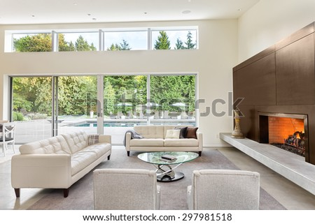 Beautiful living room in luxury home with fireplace, tv, couches - stock photo