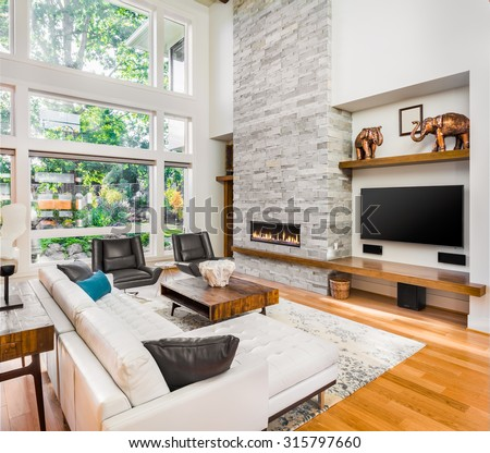 Beautiful living room interior with hardwood floors and fire in fireplace in new luxury home. - stock photo