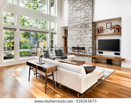 Beautiful living room interior with hardwood floors and roaring fire in fireplace in new luxury home.