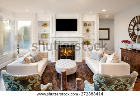 Beautiful living room with, fireplace and lit fire, couches and chairs in new luxury home - stock photo