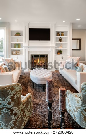 Beautiful living room with fireplace and lit fire in new luxury home - stock photo