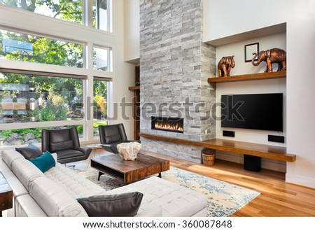 Beautiful living room with hardwood floors and fireplace in new luxury home. Has very tall vaulted ceiling and bank of windows, along with floor to ceiling fireplace and beautiful green plants outside - stock photo