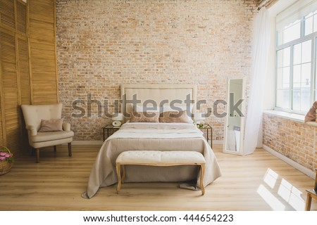 Beautiful loft bedroom with bed near brick wall