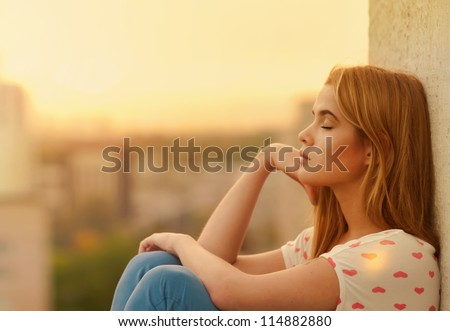 Beautiful lonely girl on the roof - stock photo
