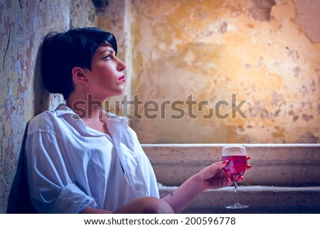 Beautiful lonely girl sitting on the steps with a glass of red wine - stock photo