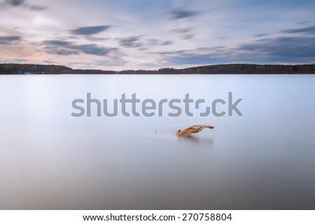 Beautiful long exposure landscape of lake in Mazury lake district (Krzywe lake near Olsztyn). - stock photo