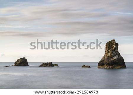 Beautiful long exposure peaceful landscape of rocks in sea - stock photo