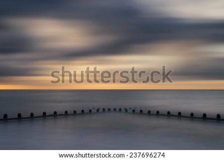 Beautiful long exposure vibrant conceptual image of ocean at sunset - stock photo
