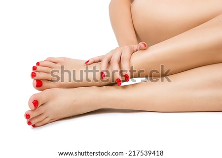 Beautiful long female bare sexy legs with red pedicure, female foots with red pedicure and hands with red manicure close up, isolated - stock photo