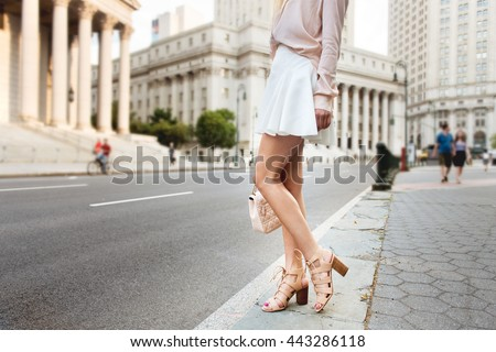 Beautiful long female legs. Beautiful woman standing on city street wearing fashionable summer outfit. Girl on high heels, white skirt, pink t-shirt holding clutch bag.