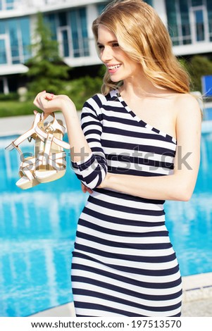 Beautiful long hair blonde female model in stripped dress posing by the pool