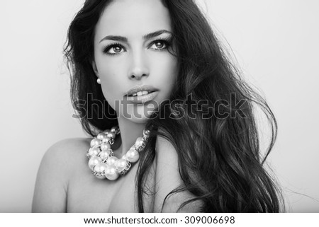 beautiful long hair brunette wearing pearl necklace, black and white portrait