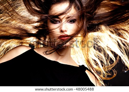 beautiful long hair brunette with hair in motion, studio shot - stock photo