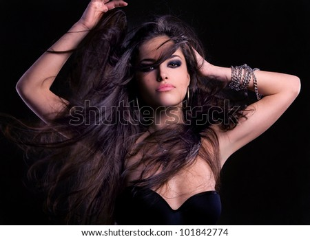 beautiful long hair brunette woman, studio dark - stock photo