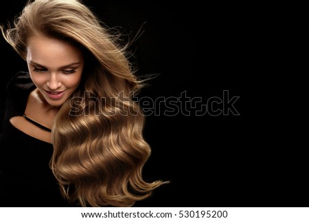 Beautiful Long Hair. Fashion Female Model With Beauty Face Makeup And Healthy Shiny Blonde Wavy Curly Hair On Black Background. Portrait Of Woman With Gorgeous Hairstyle And Hair Color. High Quality