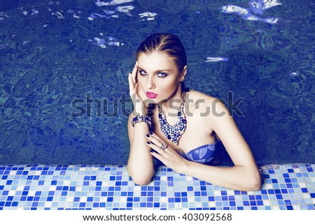 beautiful long hair female model  with bright jewelry posing by the pool - stock photo
