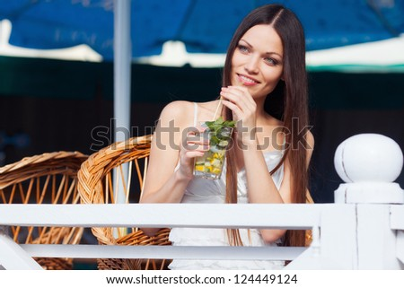 Beautiful long hair girl drinking cocktail in summer cafe