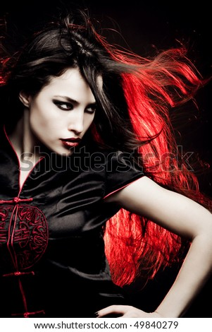 beautiful long hair woman in oriental style dress, red back light, studio shot - stock photo