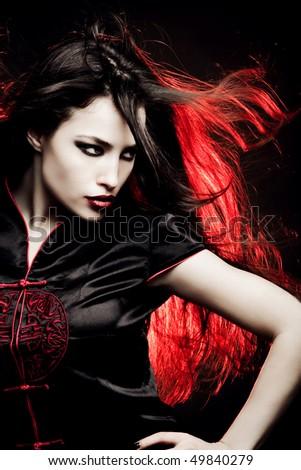 beautiful long hair woman in oriental style dress, red back light, studio shot - stock photo