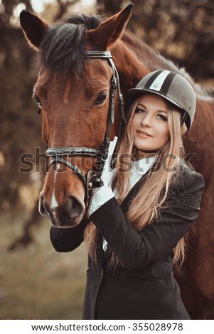 Beautiful,long-haired,blonde,friendly,joyful,loving,sweet,good,kind girl with big,calm horse horseback outdoors in summer park.She strongly loves horses,feeds,sponsors them,looks after them.Portrait - stock photo